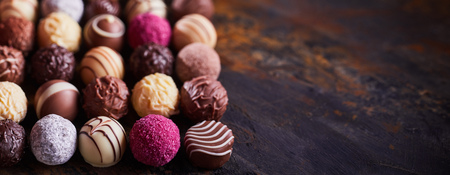 Panorama banner of assorted decorative handmade luxury chocolate balls on textured rustic or vintage wood with copy space Stock fotó