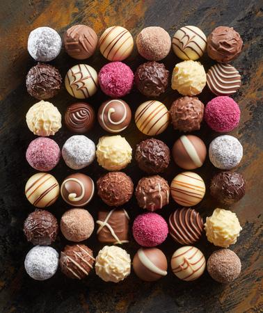 Colocación plana ordenada de bombones o bombones de chocolate de lujo dispuestos en un rectángulo en filas que muestran una amplia selección de patrones decorativos y texturas en madera rústica Foto de archivo