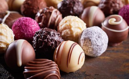 Primo piano dettaglio di una lussuosa sfera di cioccolato bianco fatta a mano in una più ampia selezione di cioccolatini speciali o praline su legno rustico Archivio Fotografico