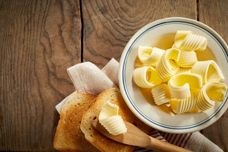 Dish of butter curls with crispy golden toast served on a rustic wood table with wooden spreader and napkin