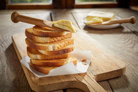 Stack of golden crispy toast on a wooden chopping board with butter and spreader balanced on top in a low angle side view on a table 스톡 콘텐츠