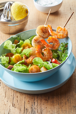 Delicious seafood salad starter with spicy grilled scampi and fresh scallops on wooden skewers served with crunchy sauteed croutons