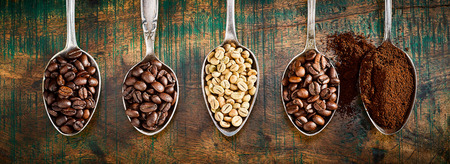 Assortment of different roasted and ground coffee beans displayed in vintage silver spoons in a panorama banner over rustic wood