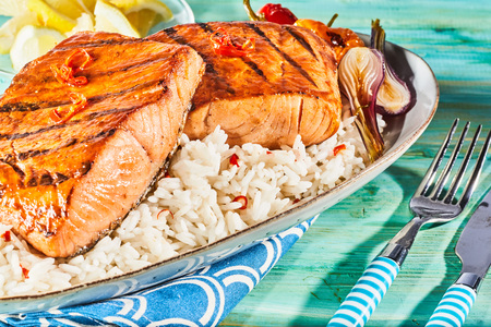 Gourmet fresh salmon steaks seasoned with chili and grilled on a barbecue served on a bed of savory rice with roasted onions Standard-Bild - 123184658