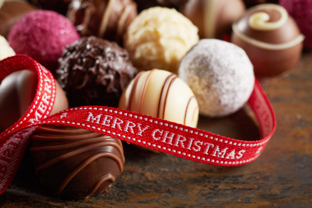 Luxury chocolate Merry Christmas festive background with a red ribbon bearing the holiday greeting twined over assorted speciality chocolate balls Stock Photo - 123184737