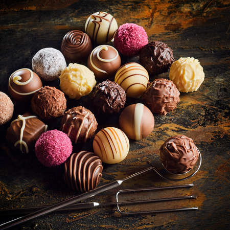 Presentation of luxury handmade chocolate bonbons in assorted decorative patterns arranged neatly on a rustic or vintage wood table with wire fork and lifter Stock Photo