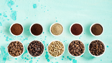 Coffee still life with roasted and raw beans and grounds neatly displayed in separate bowls in two rows on a mottled blue green background top down with copy space in banner format