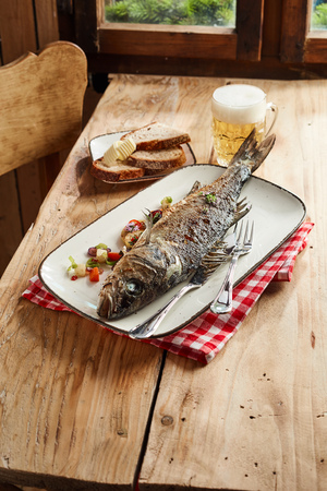 Whole oven roasted sea bass for a pub lunch served with a cold frothy beer and sliced rye bread with foreground copy space Imagens