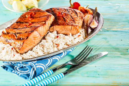 Barbecued or grilled thick fresh salmon steaks seasoned with hot cayenne chili peppers and served with roasted vegetables on a bed of rice