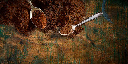 Freshly ground medium and full roast coffee in heaps with silver spoons on a rustic vintage wood background with stains and copy space in banner format