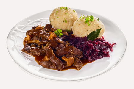 Swiss ragout from Zurich with strips of braised meat in a rich gravy with small mushrooms served with dumplings and shredded red cabbage on a generic plate isolated on white