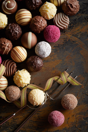 Variety of delicious gourmet handmade chocolate balls or pralines displayed in a flat lay still life on rustic wood with a wire fork and lifter with twirled gold ribbon