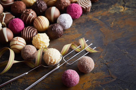 Assorted decorative handmade luxury chocolate balls or bonbons with vintage wire fork and lifter on old rustic wood for a special occasion or valentines gift