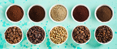 Panorama banner with assorted varieties of fresh roasted and ground coffee beans in small bowl on a mottled blue background viewed top down