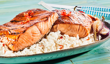 Gourmet grilled or oven-baked spicy salmon steaks with red chili on a bed of rice served with roasted onions in a close up view for a menu advertising Stock fotó