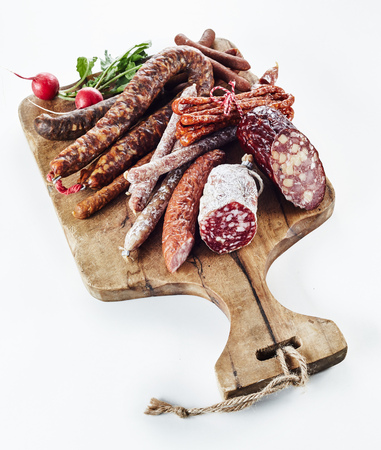 Assortment of spicy dried cured and smoked German sausages on a wooden board with fresh radishes for a tasty regional lunchtime snack isolated on white