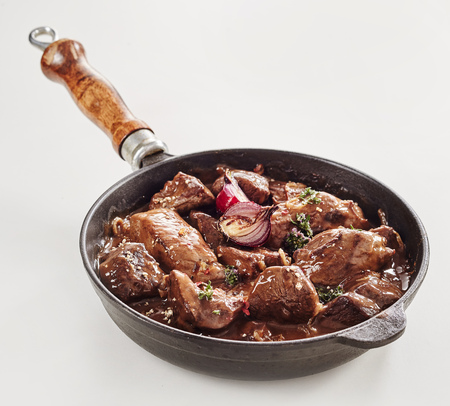 Venison hotpot or goulash with wild boar seasoned with fresh herbs and onion and served in a frying pan over white