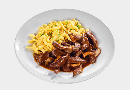 Strips of tender meat in a Swiss ragout with mushrooms and rich gravy sauce served with noodles isolated on white for menu advertising