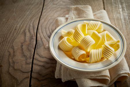 Decorative coils of farm fresh butter on a dish balanced on top of a napkin on a rustic wooden table with textured woodgrain and copy space