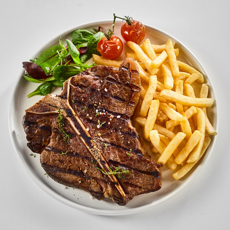 Tasty grilled or barbecued T-bone steak with fried potato chips, salad greens and roasted tomato viewed from above over white in square format 스톡 콘텐츠
