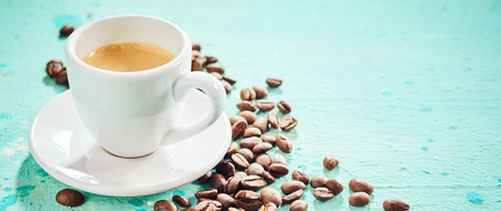 Cup of hot aromatic espresso coffee with scattered roasted beans on a blue surface Stock Photo