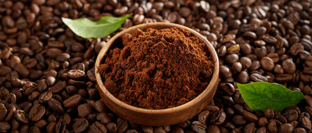 Bowl of freshly ground coffee on roasted beans Stock fotó