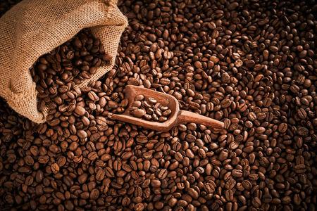 Granos de café tostado medio que se derraman de un saco con pala de madera