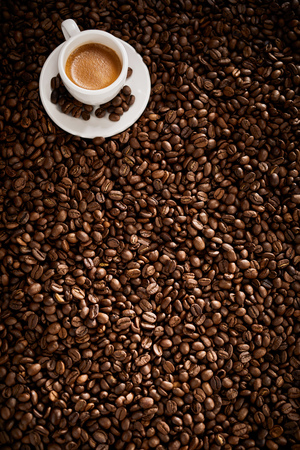 Vertical banner with roasted coffee bean background texture and a cup of frothy espresso