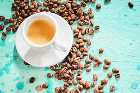 Cup of aromatic espresso coffee with scattered roasted beans on a blue background Banco de Imagens