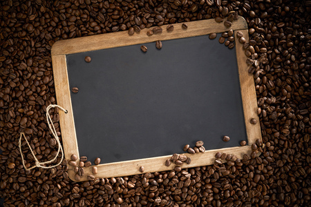 Vintage school slate surrounded by roast coffee beans with the copy space on the chalk board
