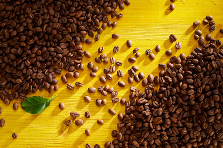 Fresh roasted coffee beans on a yellow wooden background