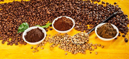 Roasted and raw beans with bowls of freshly ground coffee over a yellow wood background