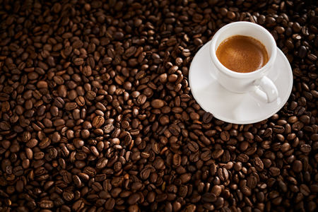 Roasted coffee bean background with a small cup of double espresso Stock fotó