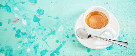 Cup of strong espresso coffee on a textured blue paint background