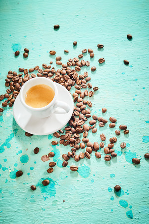 Freshly brewed espresso coffee with roasted beans over a blue background