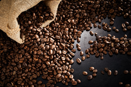 Roasted coffee beans with small burlap bag arranged in the corner