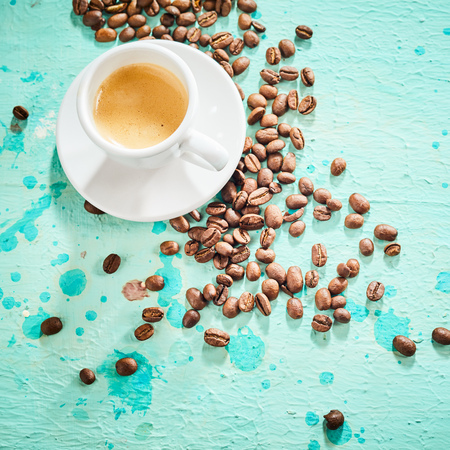Cup of espresso coffee and scattered roasted beans on blue paint background Reklamní fotografie - 124228186