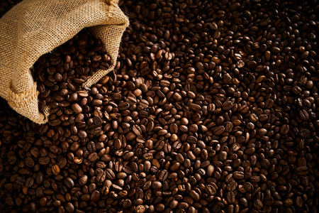 Dark roasted coffee beans spilling from a sack