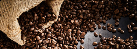 Roasted coffee beans with sack on a dark slate background Stock fotó