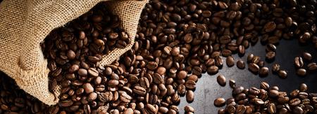 Roasted coffee beans with sack on a dark slate background Reklamní fotografie
