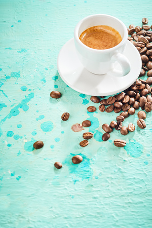 Cup of frothy espresso coffee and roasted coffee beans on blue paint background