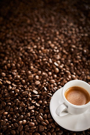 Cup of espresso coffee on a roasted bean background