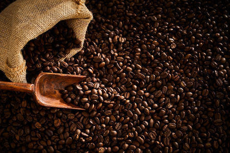 Fresh roasted coffee beans with wooden scoop and burlap sack in a full frame background Stock Photo