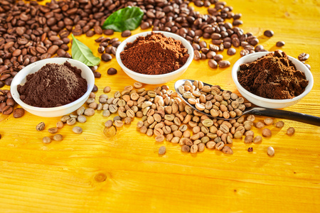 Roasted, raw coffee beans and freshly ground coffee in bowls over a stained yellow wood background