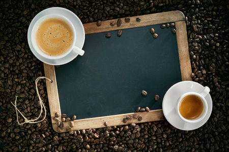 Top view of chalk board with cups of espresso and cappuccino coffee surrounded by roasted beans Stock Photo
