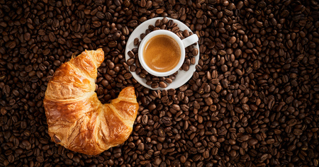 Top view of fresh croissant and cup of espresso coffee on roasted coffee beans