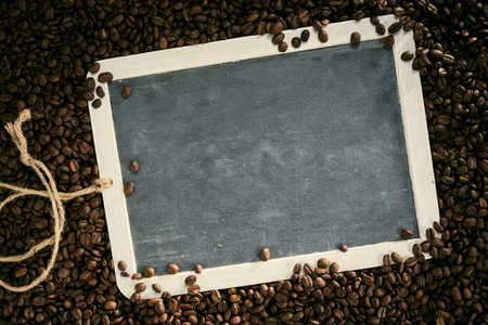 Roasted fresh aromatic coffee beans framing a blank vintage slate