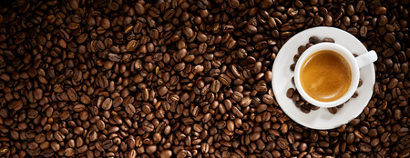 Top view of a cup of espresso coffee surrounded by roasted coffee beans