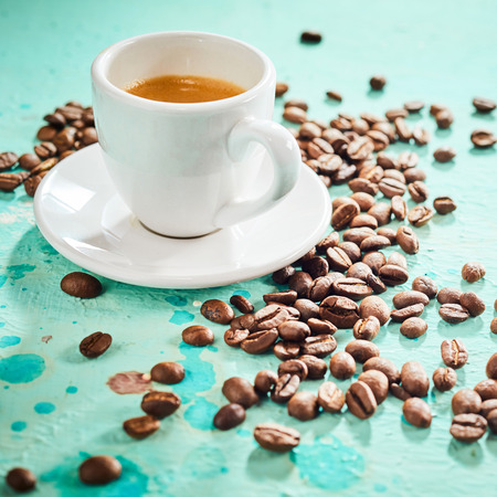 Roasted coffee beans and a cup of espresso coffee on blue painted background
