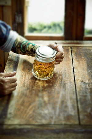 Man with tattoo on his arm seated at a table drinking a large mug of beer in a rustic pub with foreground copy space for advertising a party, festival or event Stock Photo